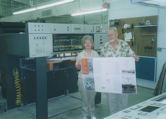 Gary and Margaret hold first printed page of book at press.